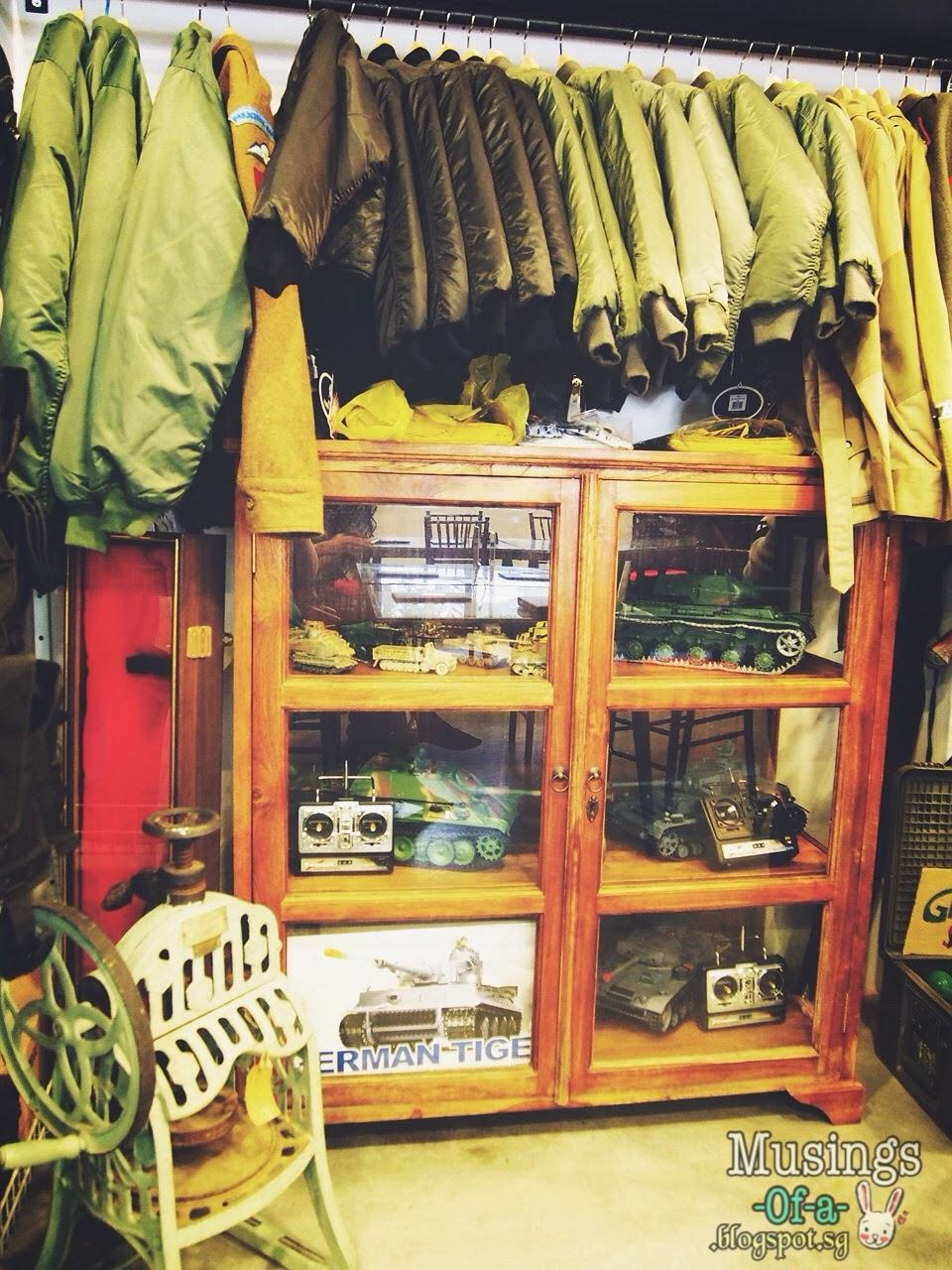 Retro Wartime Military Uniforms and Models of Tankers displayed in a wooden cabinet